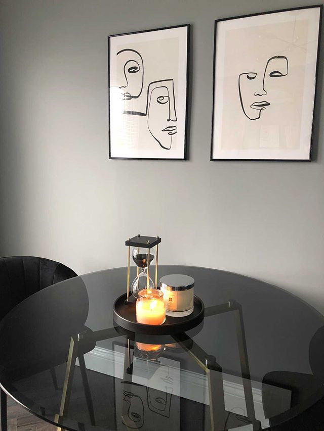 Black glass dining table with lit candles on tray