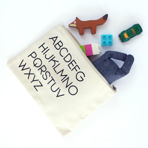 White zip pouch with alphabet printed in black. Open and spilling out toys.