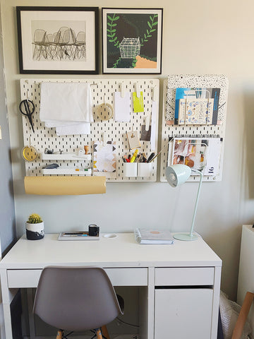 Desk with pegboard and lots of design objects
