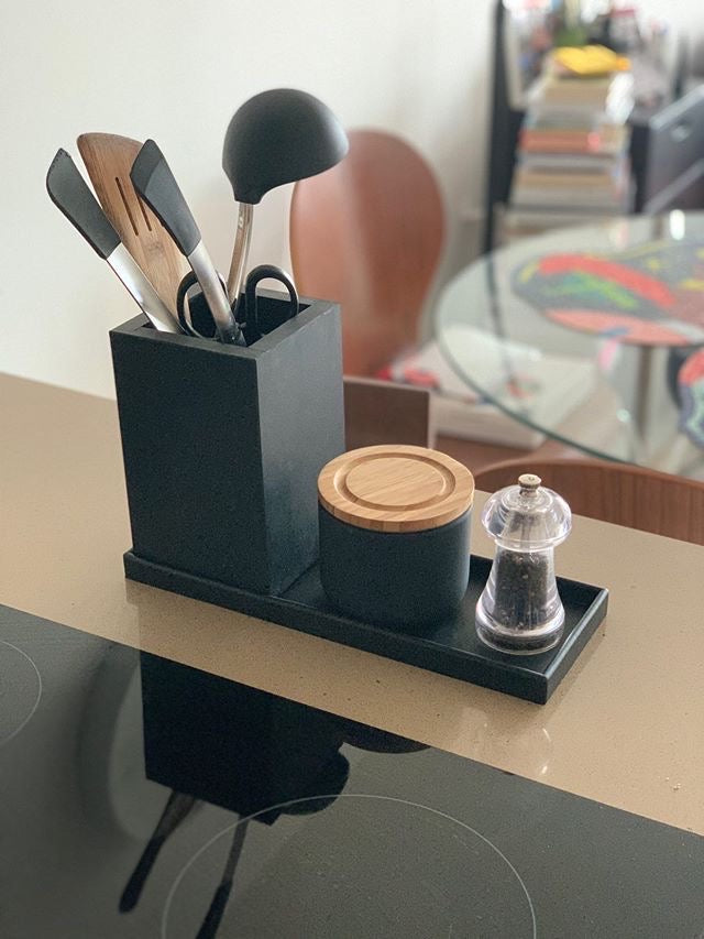 Styled black kitchen tray with utensils and condiments