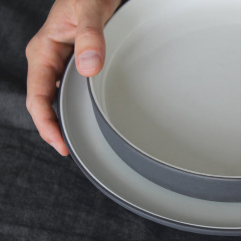 Grey and white ceramic bowl and plate, held
