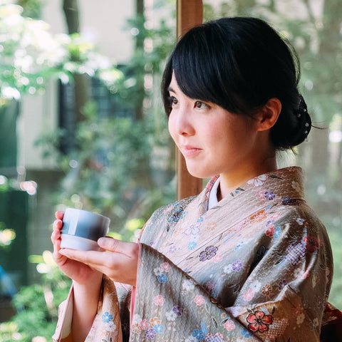 Lady in kimono holding a small gradient cup