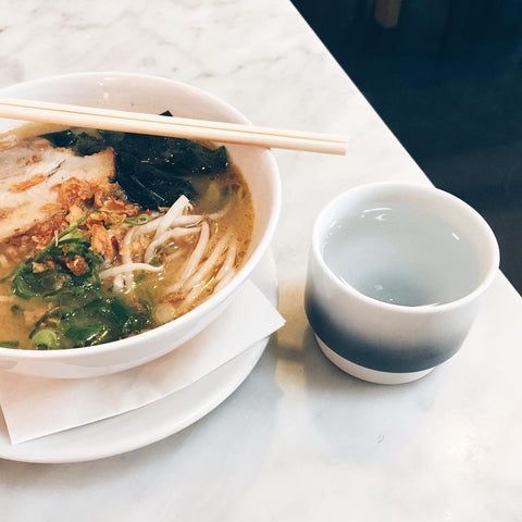 Noodle dish in a white bowl with a cup of water