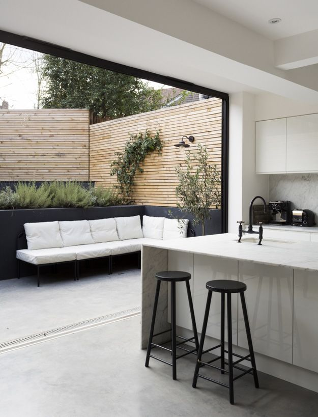 Kitchen with huge doors open to modern garden with black walls and wood cladding