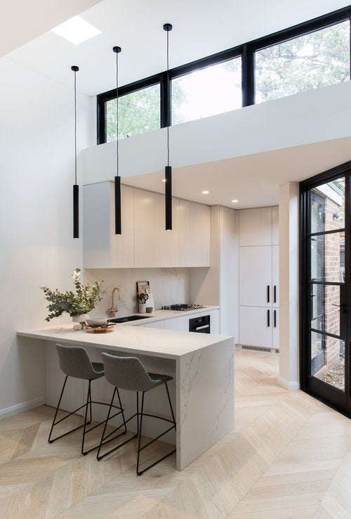 Modern kitchen with high ceilings and black framed window above