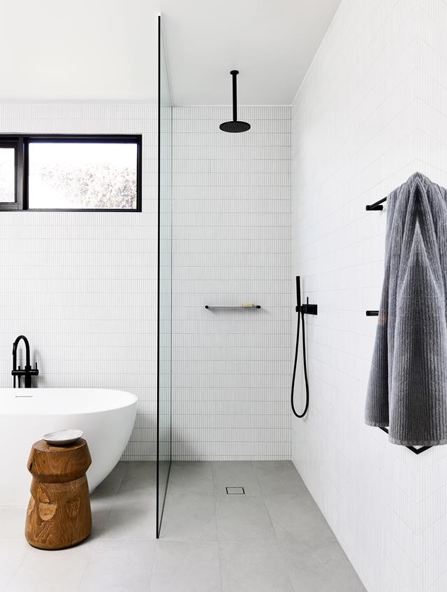 Minimal shower room with kitkat tiles, a free-standing bath and black features