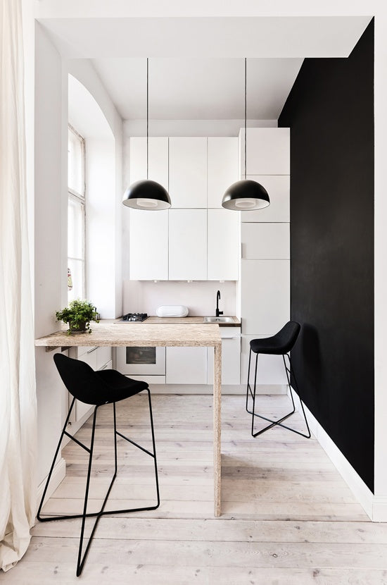 Small white kitchen, with black wall and black stools, wooden breakfast bar