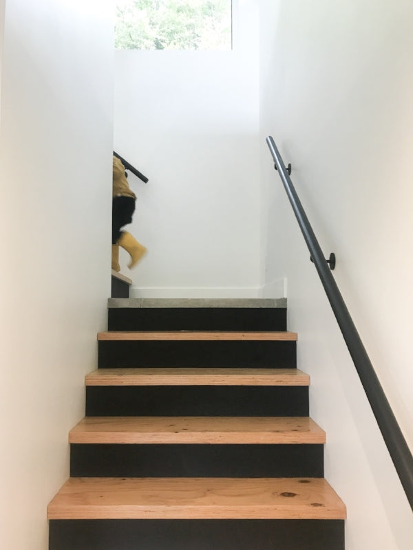 Staircase with painted black treads, child running up and disappearing around corner at top of stairs
