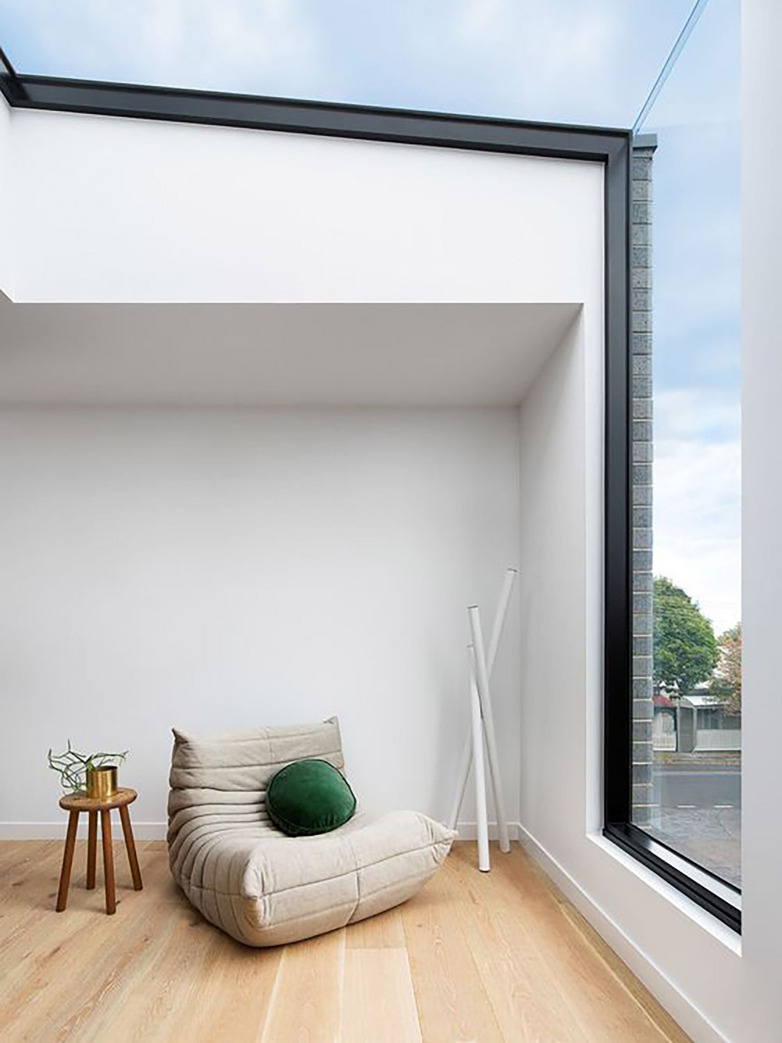 Statement window that goes up into a skylight over a large armchair