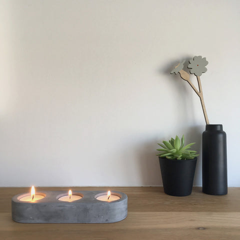 Concrete tealight holder with lit candles with a small potted succulent