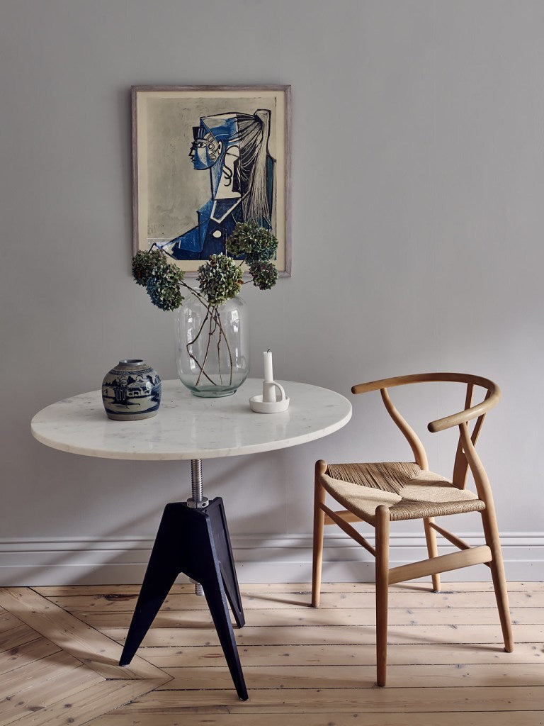 Round dining table with flowers, wishbone chair in front of a grey wall