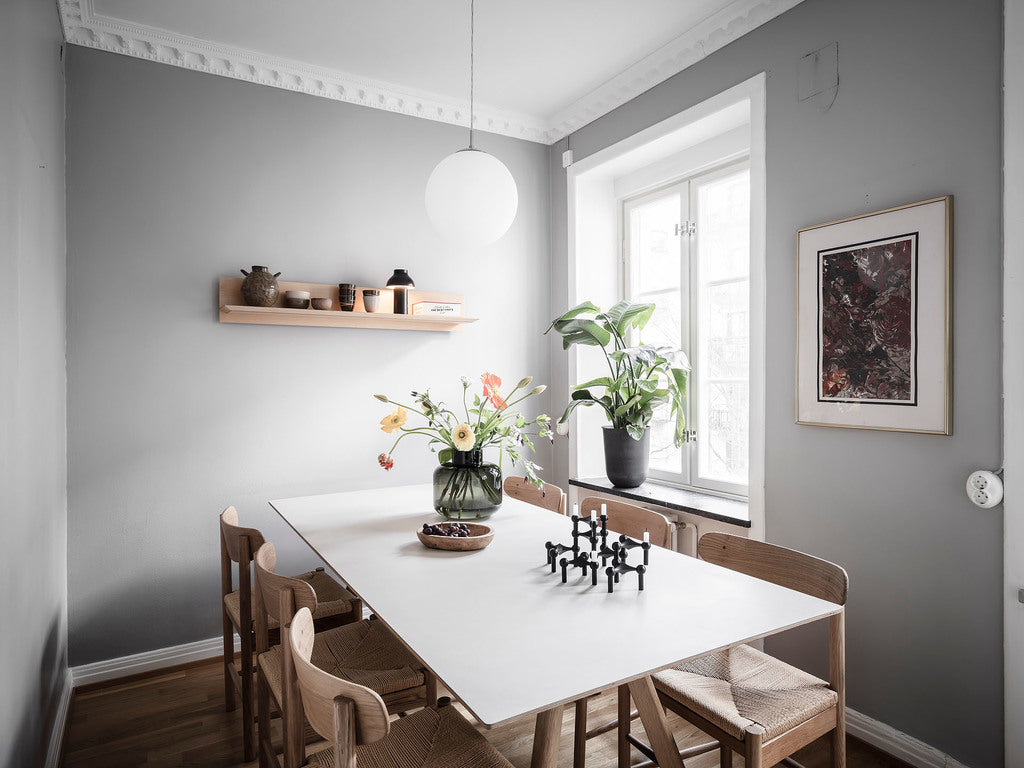 Dining table in grey painted room with classic Scandinavian dining chairs and some flowers
