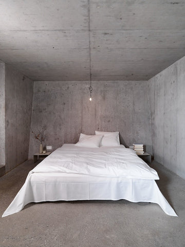 Entirely concrete bedroom with bare bulb. Double bed made up in white.