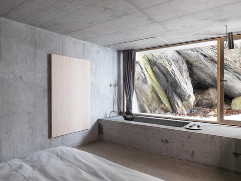 Entirely concrete bedroom with rock face outside the window