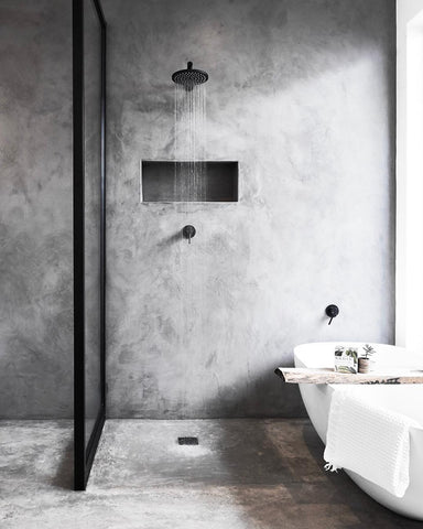 Modern concrete bathroom with white bath and shower running