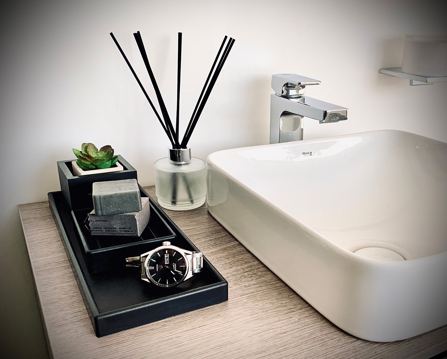 Styled bathroom tray with plant, soap, watch and diffuser