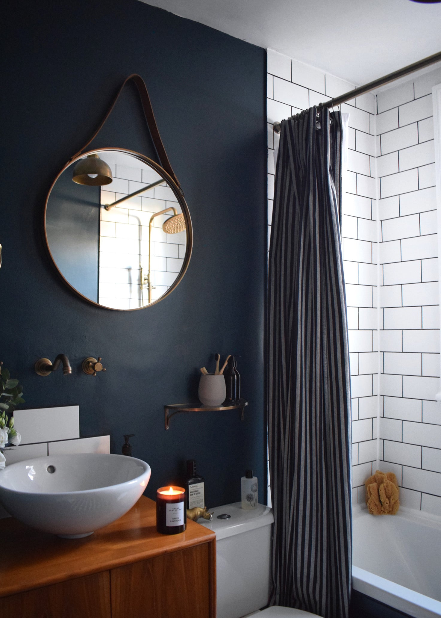 Stunning bathroom with white tiles, dark wall, round mirror, candles and other accessories