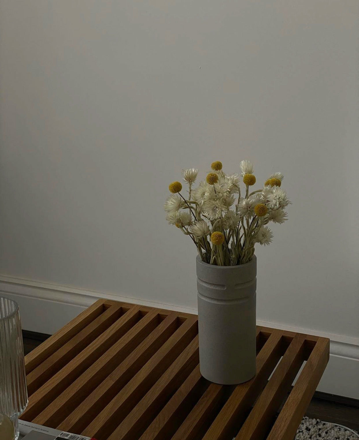 Grey jesmonite vase with preserved flower bouquet on a slatted wooden table