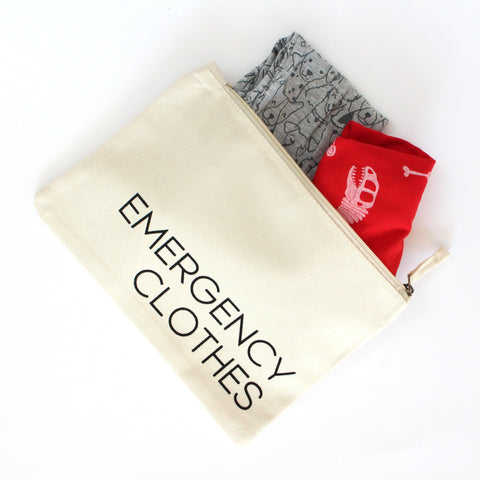 White zip pouch printed with black text. Reads: Emergency Clothes. Pouch is open and childrens clothes are spilling out