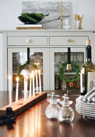 Dining table with candles and greenery