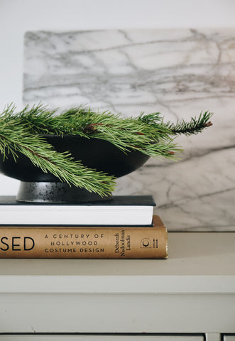Fir branch in bowl on pile of books