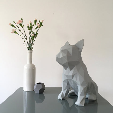 Geometric grey dog sculpture with vases and flowers
