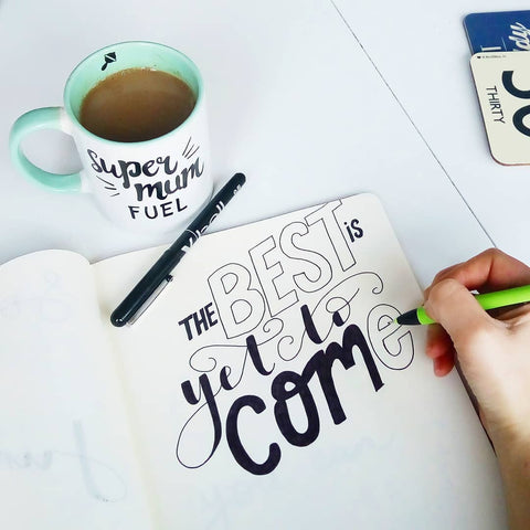 "Hand Lettering ""The Best is Yet to Come"" being coloured in. A cup of tea to one side."