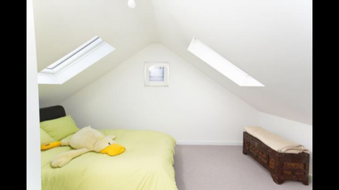 Loft bedroom with skylights and giant duck toy on the bed