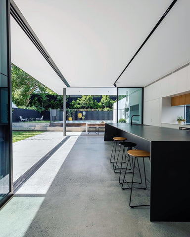 Large kitchen with concrete floor, glass walls and black breakfast bar
