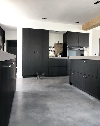 Black kitchen with polished concrete floor and a grey kitten leaping across