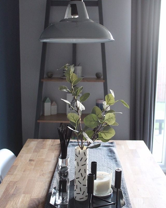 Dining table with table runner, vase and candle