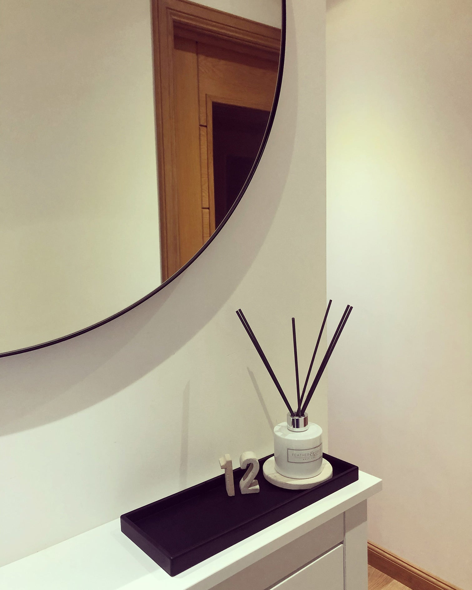 Hallway with large round mirror. Black tray with concrete number 12 and a reed diffuser