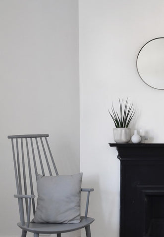 Grey chair by black mantlepiece