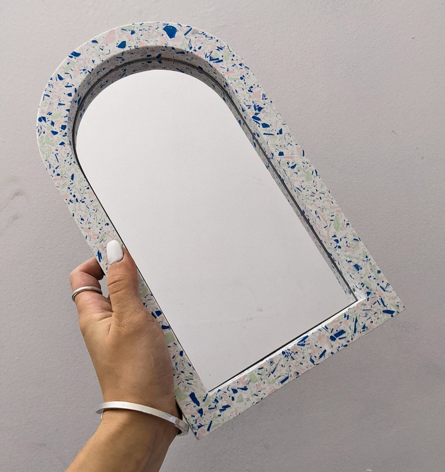 A hand holding an arched mirror with terrazzo frame