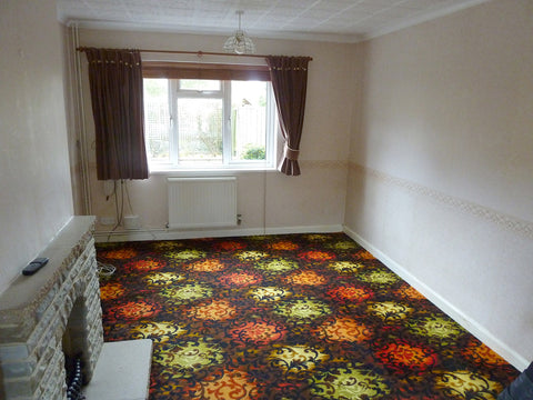 Empty living room with garish carpet and brown curtains