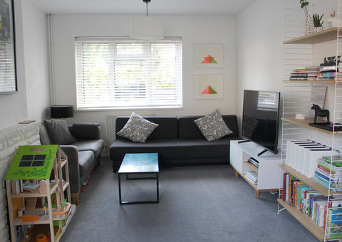 Living room with white walls, grey sofas, grey carpet, string shelves, books and toys