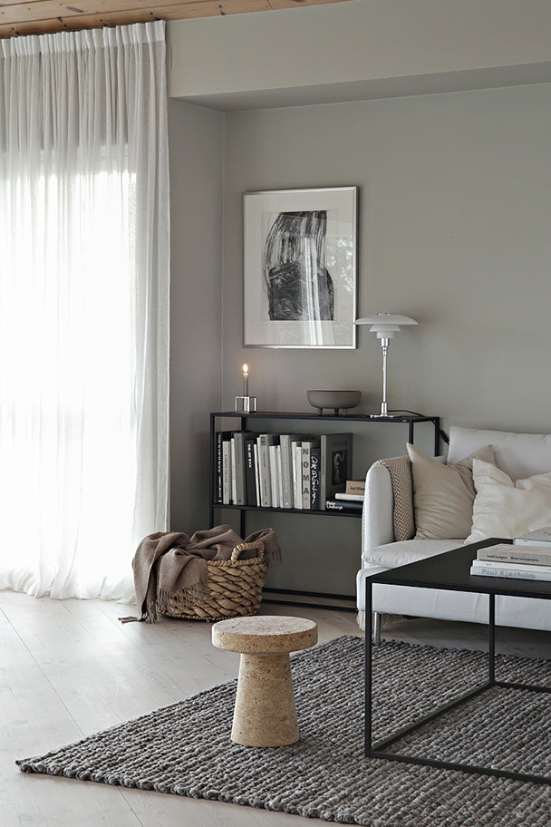 Grey living room with white sofa, black metal coffee table and a cork stool
