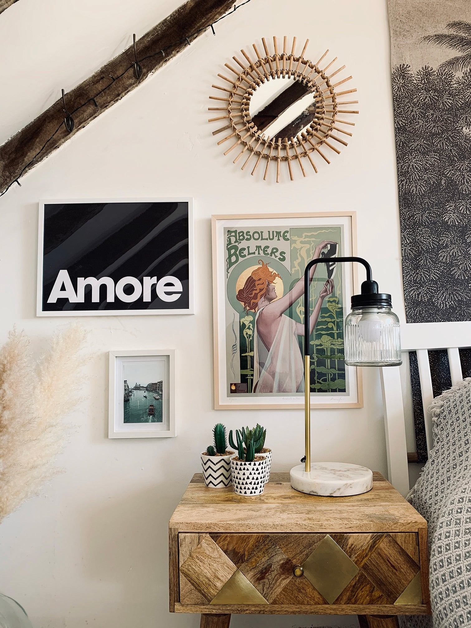 Bedside table, prints on wall, beamed ceiling