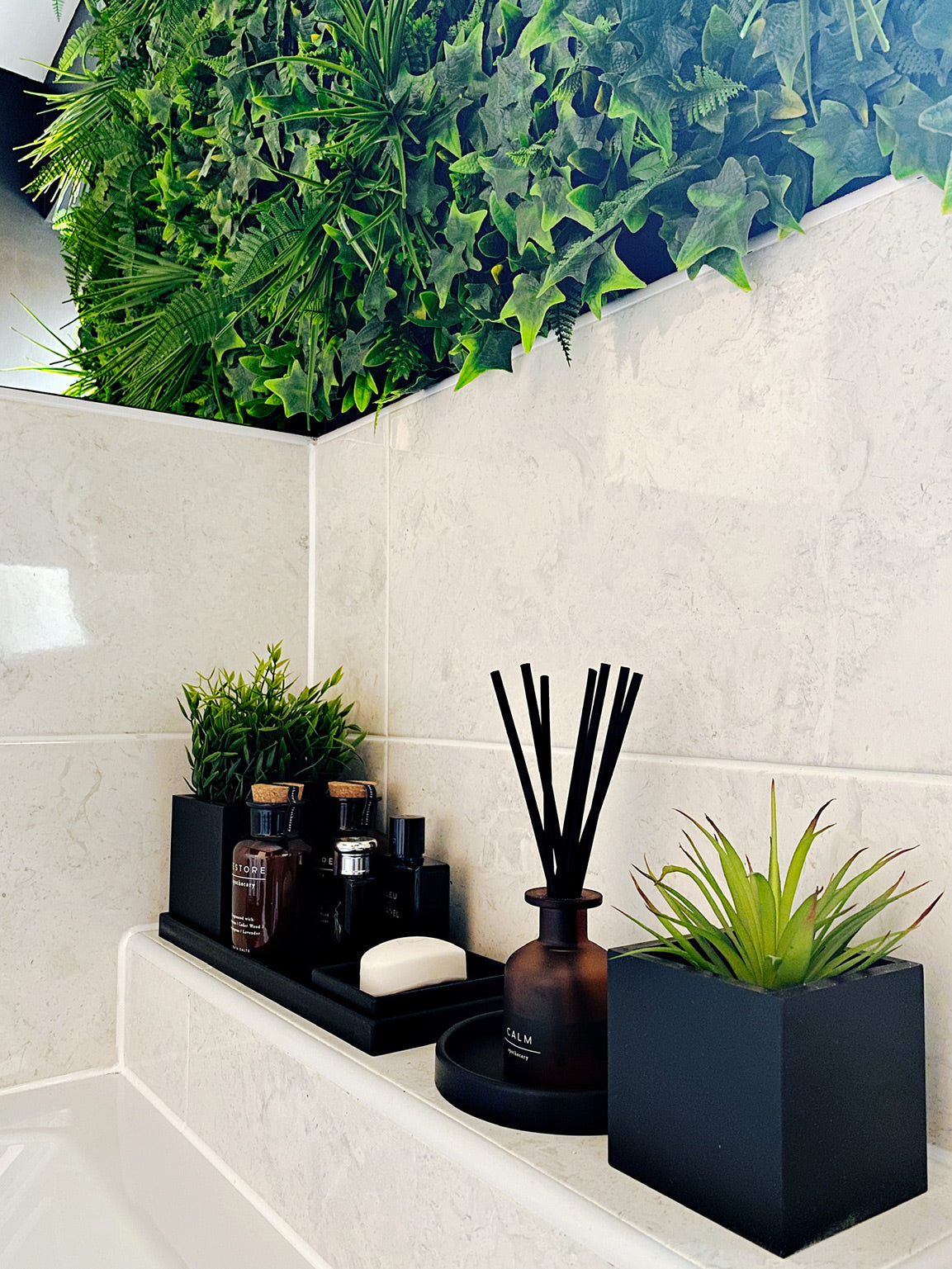 Black bathroom accessories styled with a living wall behind