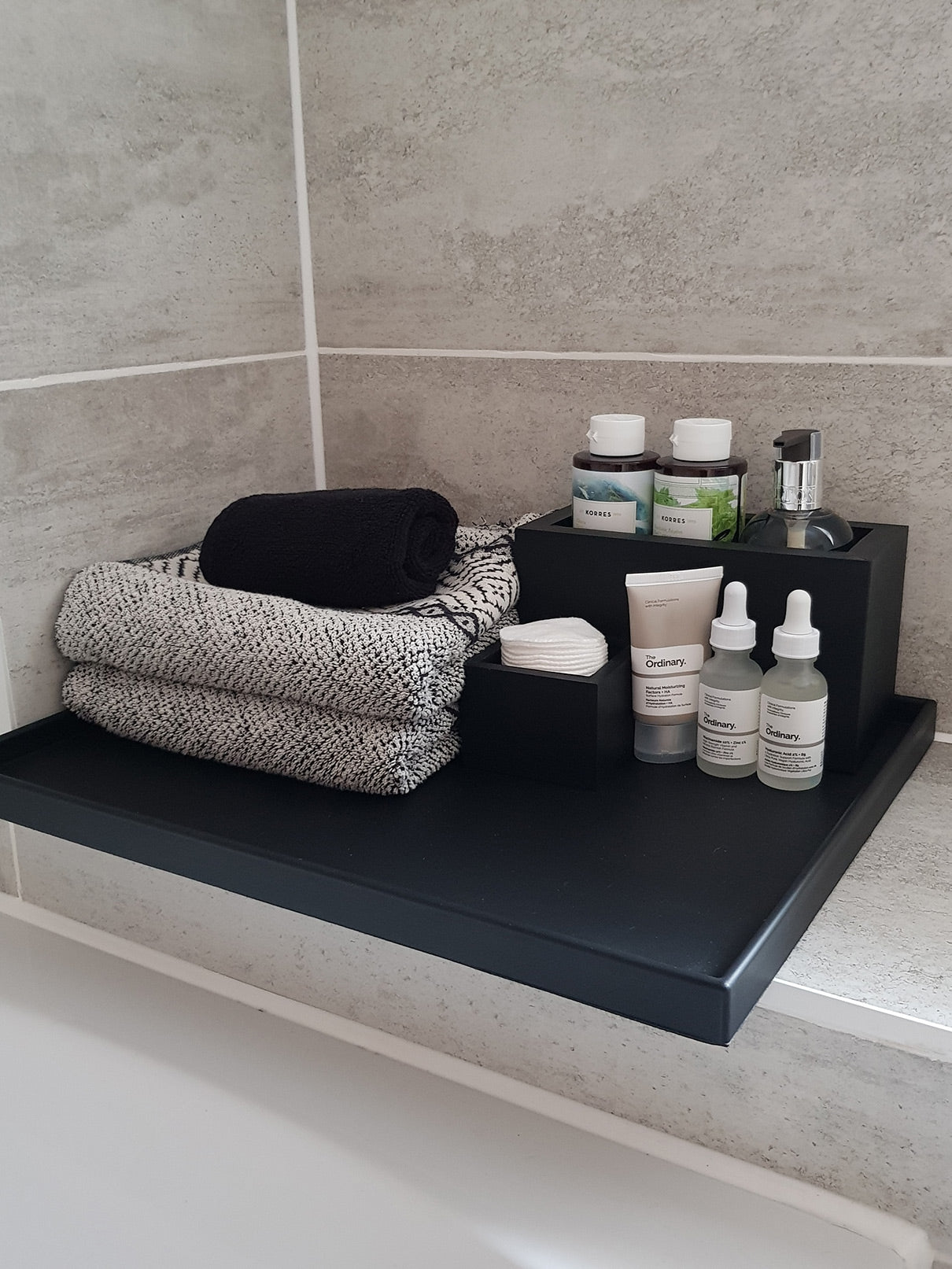 Bathroom accessories tray with towels and wellbeing products