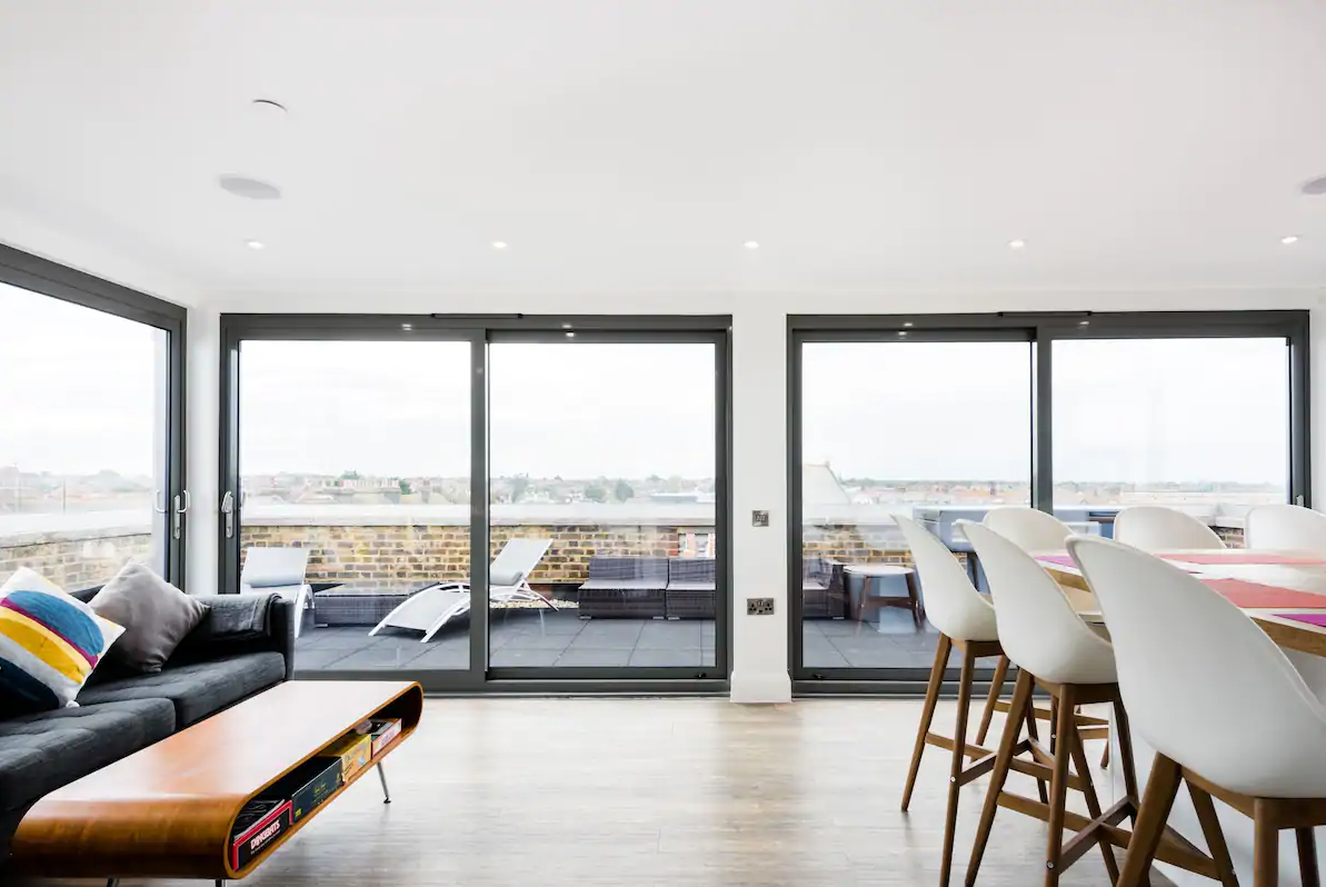 Open plan living area with wrap around windows and balcony