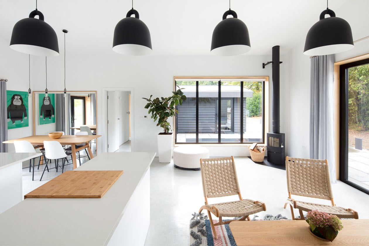 Open plan barn conversion interior. Dining and lounge areas shot from inside kitchen