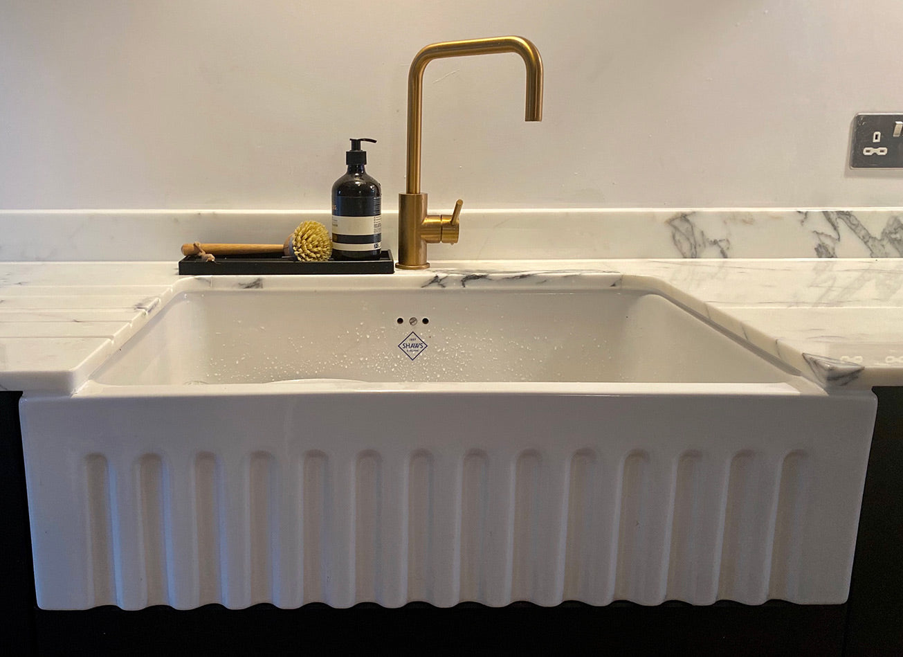 Large white sink in marble countertop with brass tap. Rubber tray with aesop hand wash