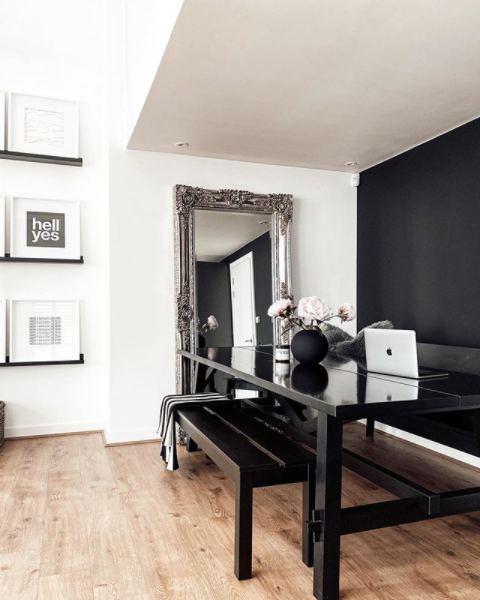 Split height dining room with gallery print wall and black furniture