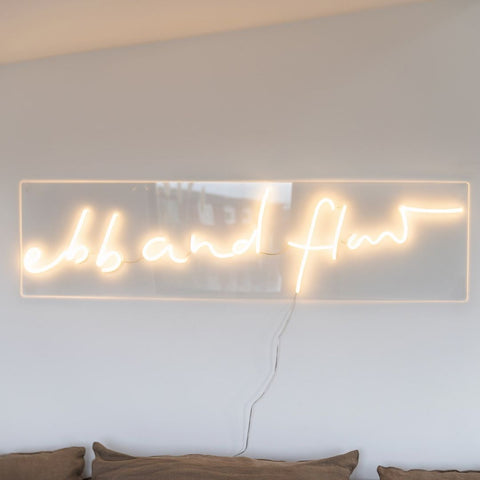 Pale neon sign, reads: ebb and flow
