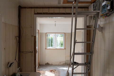 Cabin mid-renovation with ladder to ceiling