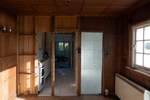 Empty shell of wood-panelled cabin, view from living room to kitchen