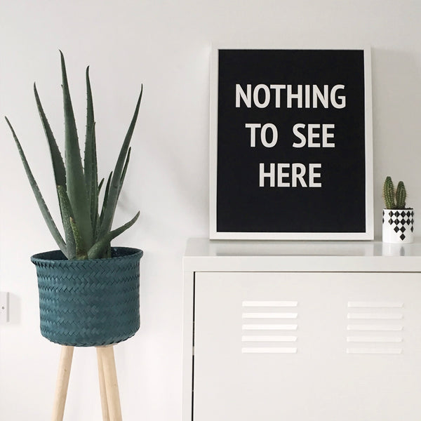 """Typographic print """"Nothing to See Here"""" white on black background. On a white sideboard next to a large plant in turquoise pot"""