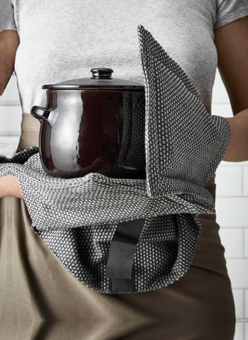 Close up, holding cooking pot with oven gloves