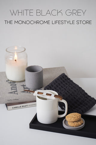 Styled lifestyle image with black tray, white mug, reusable tea bag and grey coaster with biscuits. Also grey cloth, 2 books, grey mini pot and white lit candle inside a glass jar